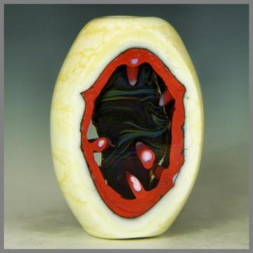 an oval lapped handmade lampwork focal bead with windows into the colorful core - Red Cavern